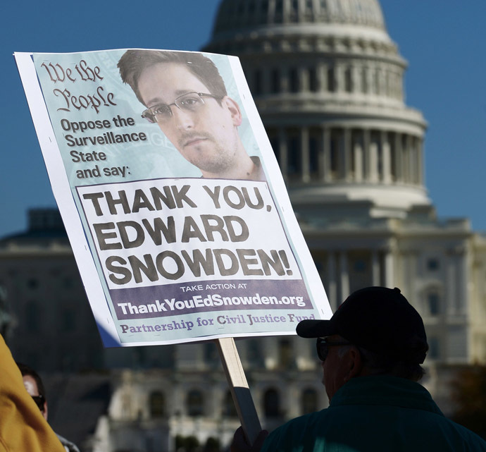Demonstrators hold placards supporting former US intelligence analyst Edward Snowden during a protest against government surveillance on October 26, 2013 in Washington, DC. The disclosures of widespread surveillance by the US National Security Agency of US allies has caused an international uproar, with leaders in Europe and Latin America demanding an accounting from the United States.    AFP PHOTO/Mandel NGAN
